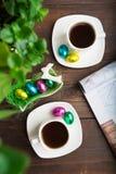 Due tazze di caffè con le uova di cioccolato nella mattina di Pasqua Fotografie Stock Libere da Diritti