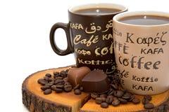 Due tazze di caffè, cuori del cioccolato e chicchi di caffè sul ceppo Fotografia Stock