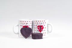 Due tazze di caffè e caramelle sotto forma di cuore su un fondo bianco - faccia colazione per gli amanti Immagine Stock Libera da Diritti