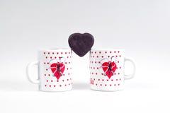 Due tazze di caffè e caramelle sotto forma di cuore su un fondo bianco - faccia colazione per gli amanti Immagini Stock Libere da Diritti