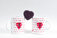 Due tazze di caffè e caramelle sotto forma di cuore su un fondo bianco - faccia colazione per gli amanti Immagine Stock
