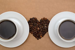 Due tazze di caffè e chicchi di caffè sotto forma di cuore Immagini Stock Libere da Diritti