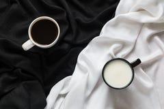 Due tazze di caffè e latti sul tessuto nero o bianco Vista superiore Fotografie Stock