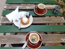 Due tazze di caffè e un bigné fotografia stock libera da diritti