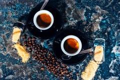 Due tazze di caffè espresso con i chicchi di caffè e dello zucchero Fotografie Stock