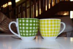 Due tazze di caffè nelle tazze verdi e gialle della tavola, piccole Fotografie Stock