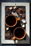 due tazze di caffè nero, di zucchero e di cioccolato su una lavagna Fotografie Stock Libere da Diritti