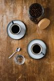 Due tazze di caffè nero e dei chicchi di caffè in barattolo sulla tavola di legno Immagini Stock