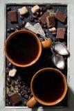 due tazze di caffè nero, di zucchero e di cioccolato su una lavagna Fotografia Stock