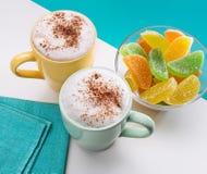 Due tazze di cappuccino con cannella e la gelatina di frutta Fotografie Stock