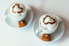 Due tazze di cappuccino con i biscotti ed i dadi contro un BAC bianco Immagini Stock