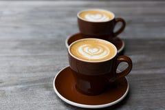 Due tazze di cappuccino con il cuore modellano l'latte-arte su fondo di legno Fotografia Stock