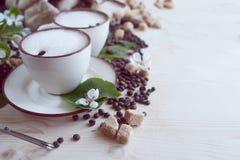 Due tazze di cappuccino di recente fatto e schiumoso Zucchero rovesciato dei chicchi di caffè, del cioccolato e di canna Immagine Stock