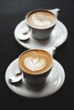 Due tazze di cappuccino sulla tavola nera Fotografia Stock