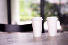 Due tazze di carta calde del caffè del caffè espresso sulla tavola nel ristorante del caffè Immagini Stock Libere da Diritti