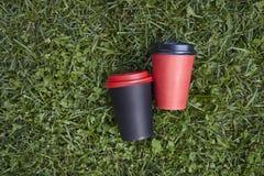 Due tazze di carta con la tazza rossa e nera del caffè portare via, sulla prima colazione all'aperto dell'erba verde Fotografia Stock Libera da Diritti