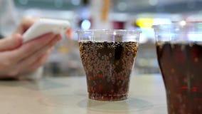 Due tazze di coca-cola sulla tavola con il messaggio della lettura della donna sul iphone alla corte di alimento stock footage