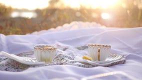 Due tazze di tè con il limone al tramonto stock footage