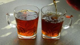 Due tazze di tè e di un getto di tè Fotografie Stock