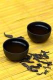 Tazze di tè cinesi e puerh selvaggio sulla stuoia gialla Fotografia Stock