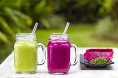Due tazze di vetro con i frullati freschi da un drago fruttificano, banana, mango, avocado, broccoli e miele Isola Bali, Ubud, In Fotografie Stock Libere da Diritti