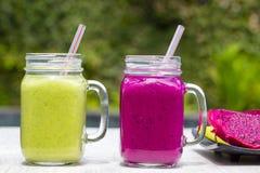 Due tazze di vetro con i frullati freschi da un drago fruttificano, banana, mango, avocado, broccoli e miele Isola Bali, Ubud, In Fotografia Stock