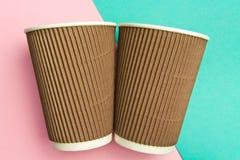 Due tazze eliminabili per le bevande calde su un rosa geometrico e sugli ambiti di provenienza del turchese Tazze di carta Immagini Stock