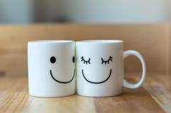 Due tazze felici sulla tavola di legno con bokeh, circa il concetto di amore Fotografie Stock Libere da Diritti