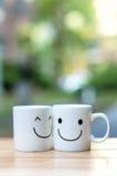 Due tazze felici sulla tavola di legno con bokeh, circa il concetto di amore Fotografie Stock