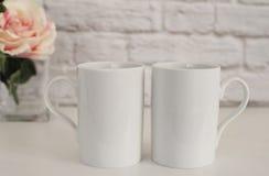 Due tazze Il bianco aggredisce il modello Derisione in bianco della tazza di caffè macchiato su Fotografia disegnata Esposizione  Fotografia Stock