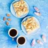 Due tazze, macinacaffè e torta di mele di caffè su fondo artistico blu fotografia stock libera da diritti