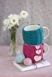 Due tazze in maglione blu e rosa con i cuori del feltro Immagine Stock