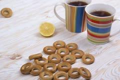Due tazze per tè con i bagel fragranti su fondo di legno Fotografia Stock