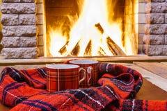 Due tazze per tè, cose di lana si avvicinano al fireplacу accogliente Fotografia Stock Libera da Diritti