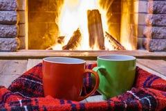 Due tazze per tè o caffè, cose di lana si avvicinano al camino accogliente Fotografie Stock Libere da Diritti