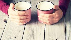Due tazze rosa con le mani del ` s della donna e del latte su una tavola di legno bianca Fotografia Stock