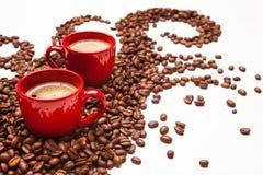 Due tazze rosse del caffè espresso con i chicchi di caffè Immagini Stock