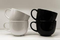 Due tazze su un fondo bianco stanno stando Immagini Stock