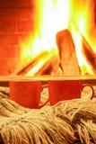 Due tazze variopinte per tè o caffè; le cose della lana si avvicinano al firep accogliente Fotografia Stock Libera da Diritti