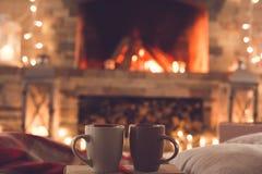 Due tazze vicino al concetto romantico di inverno del camino immagini stock libere da diritti