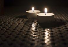Due Tealights sulla tavola all'aperto Immagini Stock