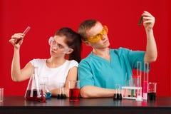 Due tecnici di laboratorio, una ragazza e un tipo, stanno tenendo le bottiglie con un liquido multicolore che lo esamina Su un fo Fotografie Stock Libere da Diritti