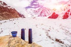 Due termo bottiglie e tazza sulla pietra e campo base dei thermoses blu di viaggio in alte montagne fotografia stock libera da diritti