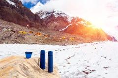 Due termo bottiglie e tazza sulla pietra e campo base dei thermoses blu di viaggio in alte montagne fotografia stock