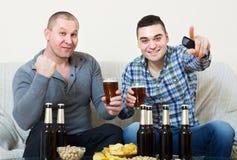 Due tifosi maschii che guardano gioco a casa Immagini Stock