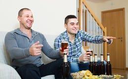 Due tifosi maschii che guardano gioco a casa Immagine Stock Libera da Diritti