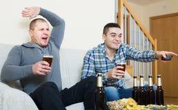 Due tifosi maschii che guardano gioco a casa Fotografia Stock Libera da Diritti
