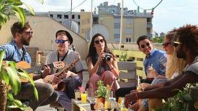 Due tipi che giocano chitarra e sassofono, ragazza che prende le foto degli amici felici archivi video