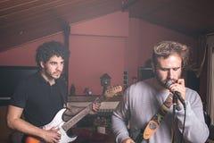 Due tipi che giocano la chitarra elettrica e che cantano immagini stock