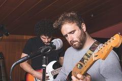 Due tipi che giocano la chitarra elettrica e che cantano immagine stock libera da diritti